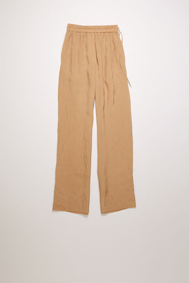 Acne Studios old pink trousers are crafted from a lightweight crinkled viscose and shaped with loose, straight legs with an elasticated waistband.