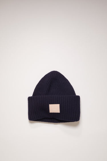 Acne Studios navy/pink beanie is rib-knitted from soft wool and accented with a face-embroidered patch on the front.