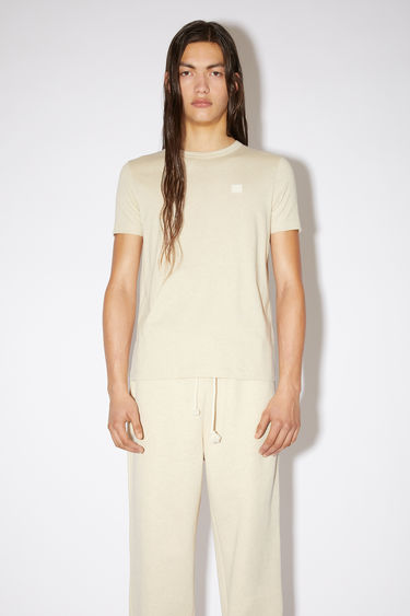 Acne Studios oatmeal melange organic cotton t-shirt features a ribbed crew neck and an embroidered tonal face patch.
