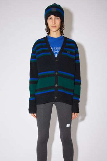 Acne Studios black/blue striped v-neck cardigan sweater is made from wool with a face logo patch and ribbed details.