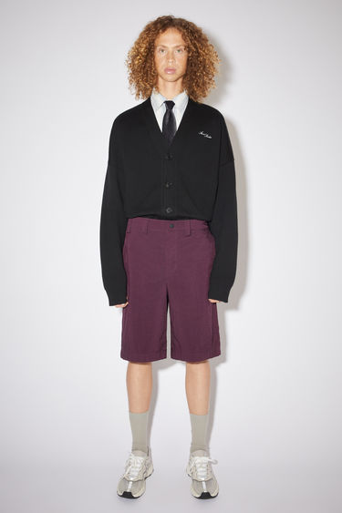 Acne Studios maroon red relaxed shorts are made of nylon with creased legs.