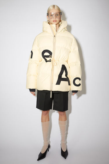 Acne Studios cream beige puffer coat is made from ripstop shell filled with recycled down and feathers and features a black logo print on the front and back. It's shaped with a padded hood and an adjustable drawstring toggle at the waist for a personalised fit.