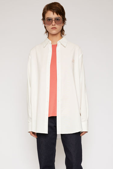 Acne Studios white shirt is cut to a boxy shape with an oversized fit and finished with a tonal face patch on the chest.