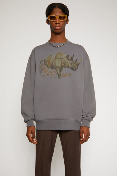 Acne Studios graphite grey sweatshirt is made from organically grown cotton and features a print of rhinos overlaid with a tonal logo. It's cut for a relaxed silhouette with a ribbed round neck and dropped sleeves.With every purchase of this item, Acne Studios makes a donation towards Save the Rhino Trust, a protection and rescue organisation that helps protect critically endangered species of similar descent and their habitats.