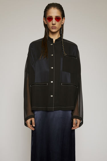 Acne Studios black blouse is crafted from sheer georgette to a boxy silhouette and features a mandarin collar and jet pockets with contrasting white topstitching along the seams.