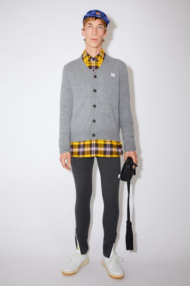 Acne Studios grey melange v-neck cardigan sweater is made from wool with a face logo patch and ribbed details.