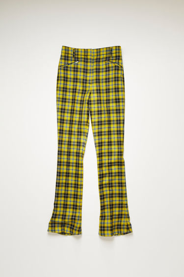 Acne Studios yellow/black tartan check trousers are tailored to a high-rise silhouette with slim legs that slightly flares from the knees and finished with two slanted jet pockets on front.