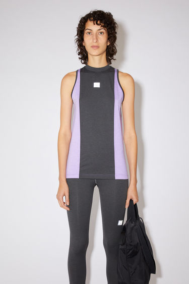 Acne Studios black colour block tank top is made of lightweight technical jersey with a reflective face logo at the chest.