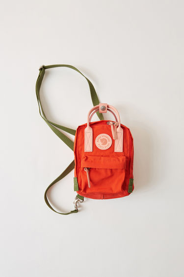 Acne Studios Kånken Clutch A/F deep orange is a micro scaled version of the classic Kånken bag, reduced down to a clutch bag size while retaining all the original details. A collaboration between Fjällräven and Acne Studios, with co-branded details.
