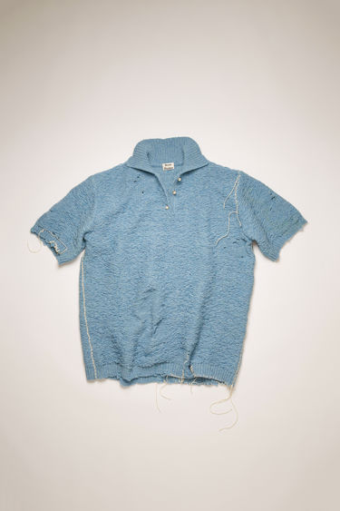 Acne Studios sky blue sweater is crafted from wool to an oversized fit with quarter-length button placket and wide short sleeves and features heavy distressing and whipstitching along the hem and sleeves.