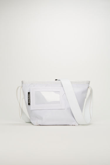 Acne Studios white crossbody bag is crafted to a structured rectangular shape with a transparent card pocket on front and features an adjustable shoulder strap.