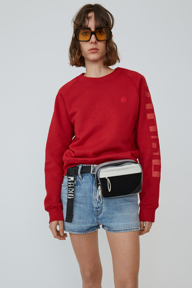Acne Studios Blå Konst cardinal red raglan sleeve sweatshirt with branding down one sleeve.