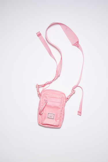 Acne Studios bright pink pocket bag is made from technical ripstop with a detachable crossbody strap and an array of zipper and mesh pockets, accented with a polished metal logo plaque with a face motif in black.