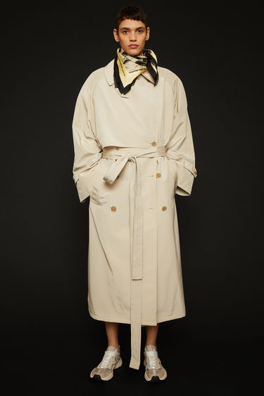 Acne Studios cold beige trench coat is cut to a raglan-sleeved silhouette and features a matching belt and an oversized back storm flap.