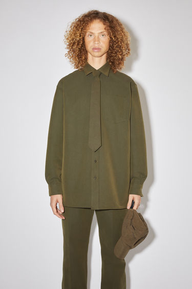 Acne Studios hunter green oversized shirt is made of a matte cotton blend with a relaxed fit.
