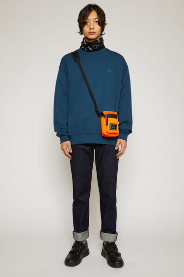 Acne Studios midnight blue sweatshirt is crafted from midweight loopback jersey to an oversized silhouette with dropped shoulders and accented with a tonal face-embroidered patch on the chest.
