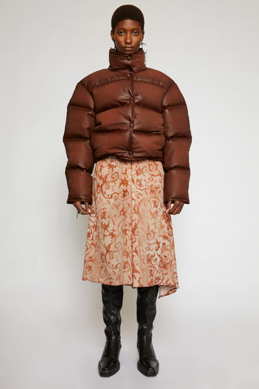 Acne Studios rusty brown down jacket is cut to a cocoon shape from leather and filled with recycled down and feathers.