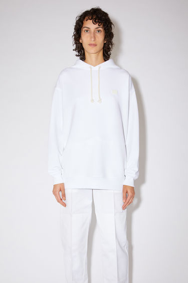 Acne Studios optic white oversized hooded sweatshirt is made of organic cotton with a face logo patch and ribbed details.