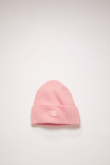Acne Studios Mini Pansy N Face blush pink beanie is rib-knitted from soft wool and accented with a tonal face-embroidered patch at the cuff.