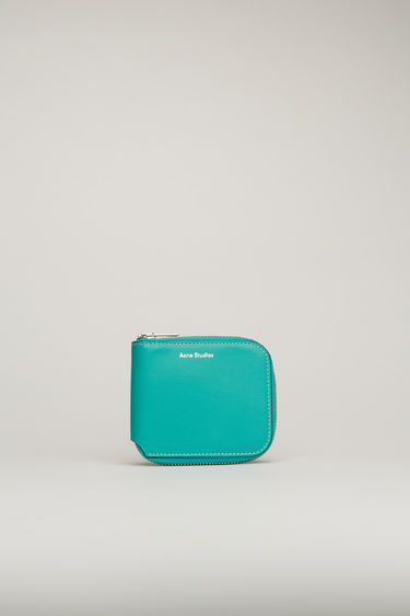 Acne Studios turquoise blue wallet is crafted from soft grained leather to a bi-fold design and has a wraparound zip that opens to reveal two card slots and a note sleeve.