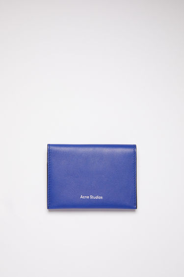 Acne Studios blue multi colour block bifold card holder is made of soft grained leather with four card slots and a silver stamped logo on the front.