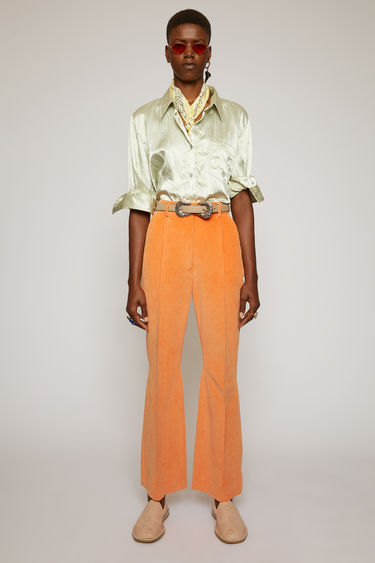 Acne Studios peach orange corduroy trousers are cut slim through the hips and feature cropped, kick-flare legs with pressed creases for a refined finish.
