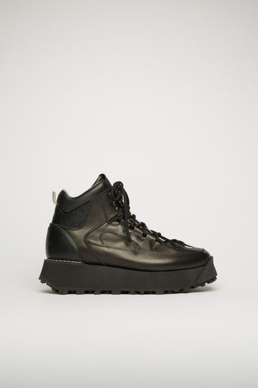 Acne Studios black boots take cues from functional elements of hiking gears. They're crafted from soft grained leather with a padded ankle cuff and rubber heel cap, then set on a lug sole.