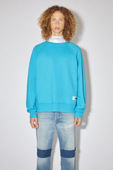 Acne Studios bright blue raglan sleeve sweatshirt is made of a cotton blend with a label at the bottom side.