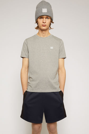 Acne Studios light grey melange t-shirt is cut from a lightweight cotton jersey to a slim-fitting silhouette with a round neckline and accented with a tonal face-embroidered patch on the chest.