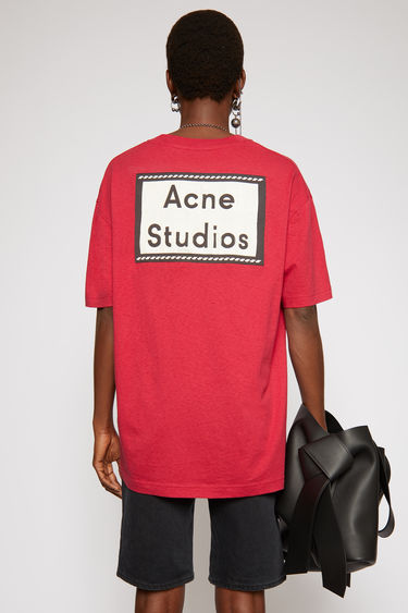 Acne Studios fuschia pink t-shirt is crafted from cotton jersey to an oversized silhouette and adorned with a label patch on the sleeve.