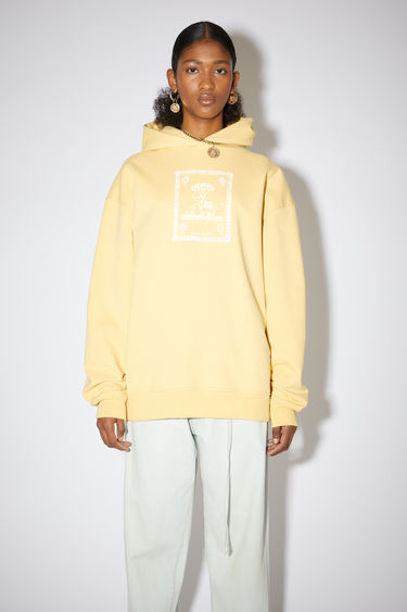 Acne Studios vanilla yellow oversized hooded sweatshirt is made of organic cotton with a printed design on the front.