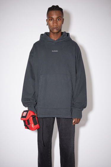 Acne Studios black oversized hooded sweatshirt is made of cotton and features an Acne Studios logo on the front.