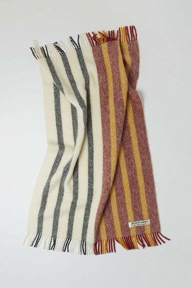 Acne Studios launches an exclusive range with Swedish artist Jacob Dahlgren. As part of the collaboration, the burgundy multi striped blanket is finely knitted from brushed wool and trimmed with fringed edges.