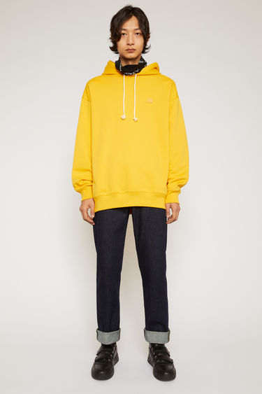 Acne Studios honey yellow hooded sweatshirt is crafted from midweight loopback jersey to an oversized fit and accented with a tonal face-embroidered patch on the chest.