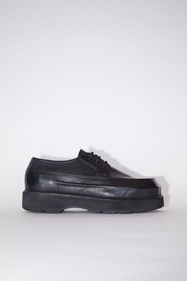 Acne Studios black lace-up derby shoes are made of leather, inspired by boat shoes.