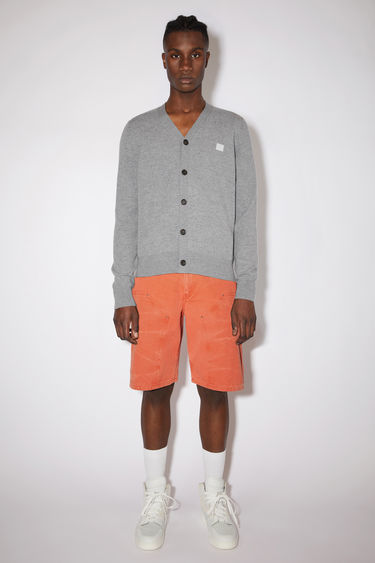 Acne Studios light grey melange v-neck cardigan sweater is made from wool with a face logo patch and ribbed details.