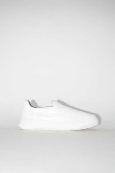 Acne Studios white/optic white chunky slip-on sneakers are made of leather with a face logo on the back.