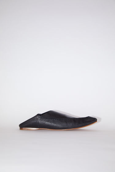 Acne Studios black are flat slip-on shoes made of leather, inspired by Moroccan babouche slippers.