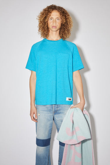 Acne Studios bright blue short sleeve raglan t-shirt is made of a cotton blend with a logo label at the bottom side.