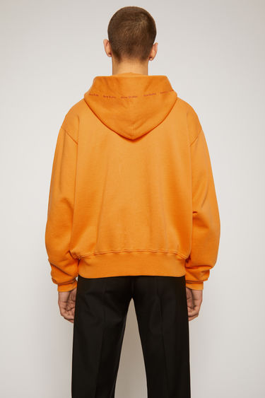 Acne Studios peach orange sweatshirt is made from organically grown cotton and features the tonal logo along the drawstring hood. It's designed to fall loose over the frame with dropped shoulders.