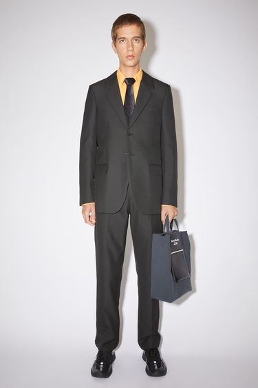 Acne Studios black suit jacket is tailored to a single-breasted silhouette with stitched darts through the waist and has notch lapels and lightly padded shoulders.
