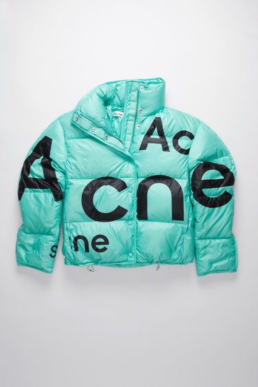 Acne Studios turquoise blue down jacket is crafted to a cocoon shape with a packaway hood, drawstring hem and features a black logo print on the front and back.