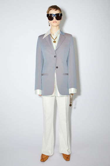 Acne Studios blue/brown constructed suit jacket is made of an changeant wool with a fitted waist and elongated silhouette.