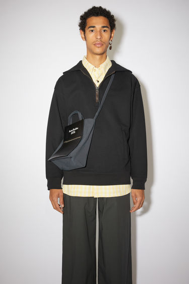 Acne Studios black hooded sweatshirt is made from organically grown cotton and recycled polyester that's enzyme-washed for a soft handle. It's cut for an oversized fit and features a half-zip closure and a kangaroo pocket.