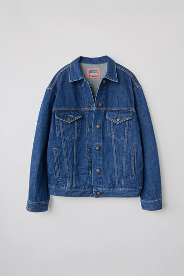 Acne Studios 2000 Dark Blue Trash denim jacket is crafted from rigid denim with a dark blue stone wash. It is finished with chest flap pockets and untrimmed button holes. This style is designed for an oversized fit.