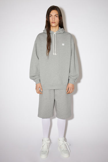 Acne Studios light grey melange hooded sweatshirt is crafted from midweight loopback fleece to an oversized fit and finished with a tonal face patch on the chest.