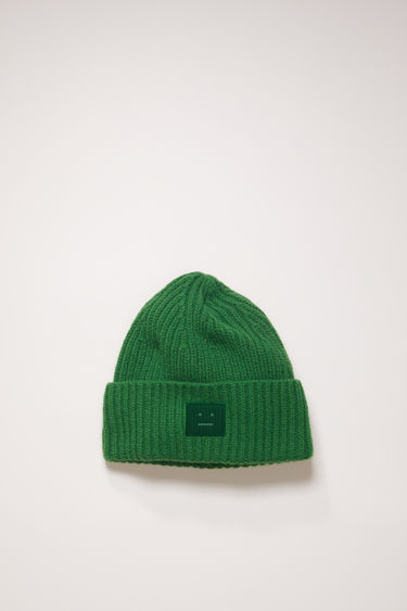 Acne Studios deep green beanie is knitted in a thick rib-stitch from soft wool and features a tonal face-embroidered patch on the turn-up.