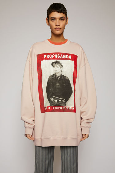 Acne Studios champagne beige sweatshirt is crafted for an oversized fit from midweight loopback jersey and features prints from the Propaganda Magazine.