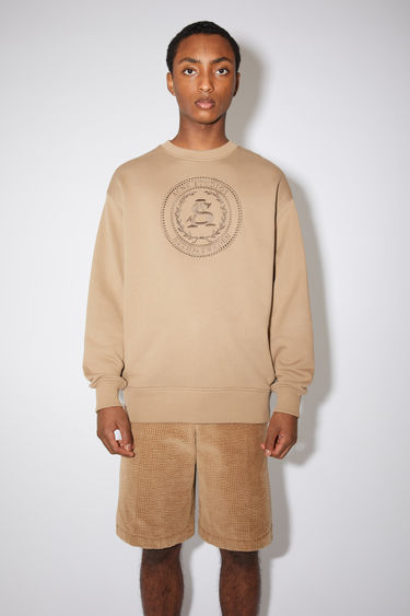 Acne Studios light brown oversized sweatshirt is made of cotton with an embroidered logo design on the front.