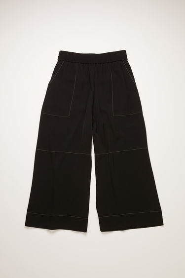 Acne Studios black culottes are crafted from fluid twill with an elasticated mid-rise waist and wide cropped legs defined with contrasting white topstitching.